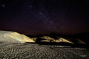 Under a moonless night sky in Death Valley California, headlights from a passing car light the barren landscape at Zambriske Point making it seem as though one is standing on another planet looking out into the universe.  The upper left star cluster is the Pleiades (also known as the Seven Sisters or Messier object 45) which is a 100 million year old formation approximately 130 parsecs (424 light-years) from earth.<br /> <br /> Zabriskie Point is part of the Amargosa Range located on the eastern side of Death Valley.  The area is noted for its erosional landscape, composed of sediments from Furnace Creek Lake, which dried up 5 million years ago—long before Death Valley came into existence.  This ancient lake began forming approximately nine million years ago. During the several million years of the lake's existence, sediments composed of saline muds, mountain gravels, and ashfalls from the then-active Black Mountain volcanic field collected at the bottom of the lake.<br /> <br /> Camels, mastodons, horses, carnivores, and birds left tracks in the lakeshore muds, along with fossilized grass and reeds. Borates were concentrated in the lakebeds from hot spring waters and decomposition of rhyolite in the nearby volcanic fields. Indeed, the location is named after Christian Brevoort Zabriskie, vice-president and general manager of the Pacific Coast Borax Company in the early 20th century. The company's twenty-mule teams were used to transport borax from its mining operations in Death Valley.