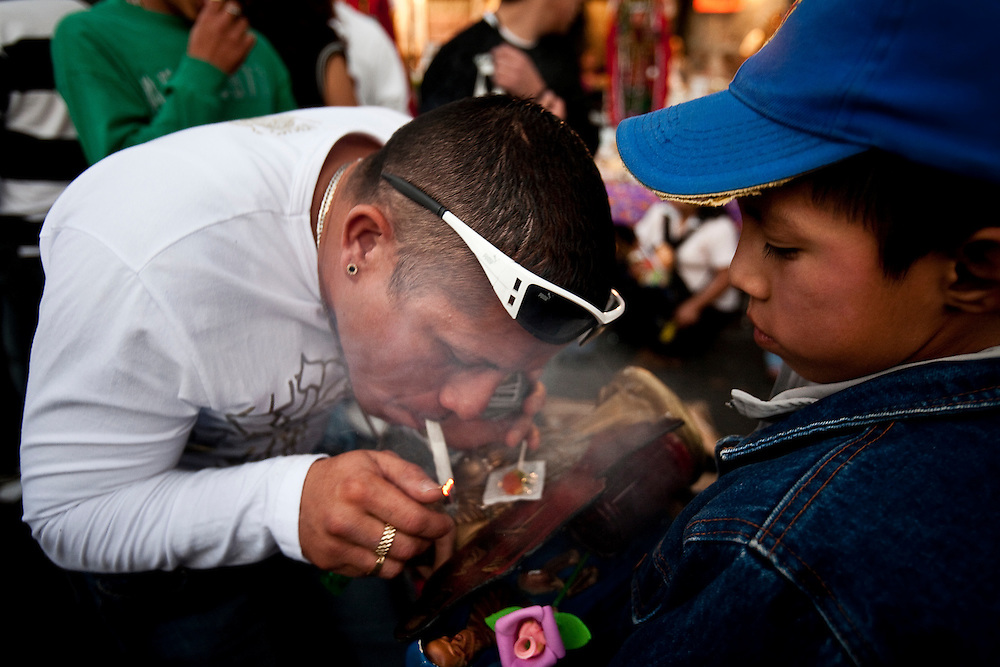 A Sante Muerte devotee blows marajuana smoke at a figure held boy in front of a popular shrine in Tipito in Mexico City.