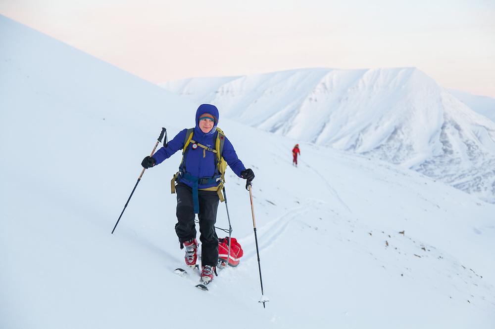 Mylène Jacquemart pulls a ski sled across Breinosa above Adventdalen, Svalbard at dawn.