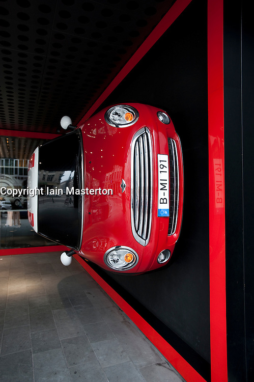 Red mini car fixed to wall at entrance to Mini Shop on Friedrichstrasse in Mitte Berlin