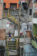 """2015/11/23 - Medellín, Colombia: Two girls walk down the stairs of barrio Pablo Escobar in Medellín. Originally called """"Medellin Sin Tugurios,"""" or Medellin Without Shanty Towns, Barrio Pablo Escobar is located high up on the eastern slope of Medellin, where Pablo Escobar built 400 houses, which he gave to poor people that used to live in a mountain of garbage in the Moravia barrio. (Eduardo Leal)"""