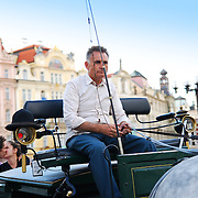 A coach on Prague Stare Mesto Square with a couple kissing.