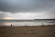 """Community volunteers battle rain and wind to draw the face of Poet & Soldier Wilfred Owen on the beach in Folkestone as part of Danny Boyle's 'Pages of the Sea""""  Armistice Day event commemorating 100 years since the end of the First World War on remembrance day the 11th of November 2018. Sunny Sands beach, Folkestone, Kent, United Kingdom."""