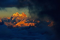 Russia, Caucasus, Mt. Ushba (4710 m asl), just on the Georgian side of the border, is lit by red light just before sunset. The valley below is covered by clouds and fog.<br /> Seen from Elbrus.