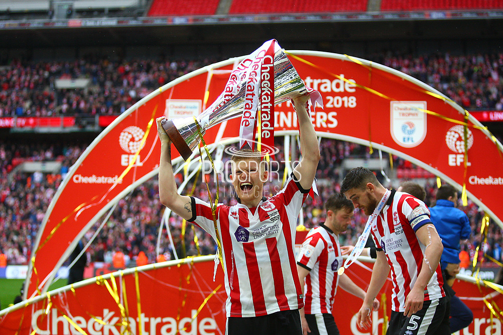 Lincoln City's match winner Elliott Whitehouse lifts the Checkatrade Trophy during the EFL Trophy Final match between Lincoln City and Shrewsbury Town at Wembley Stadium, London, England on 8 April 2018. Picture by John Potts.