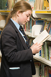 Secondary school student looking at books in the school library,