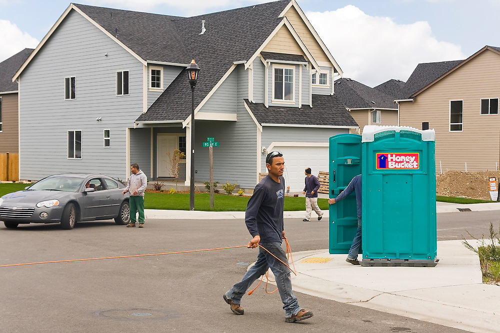 Construction workers put the finishing touches on a new housing development in Tacoma, Washington.
