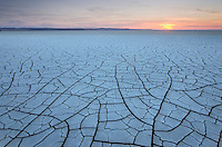 Setting sun on patterns of cracked mud on dry lakebed of Harney Lake, Malheur National Wildlife Refuge, Oregon