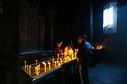Visitors light candles and pray at the Monastery of Geghard pictured on Sunday, Dec 27, 2020. With its remarkable rock-cut churches and tombs, it is an exceptionally well preserved and complete example of medieval Armenian monastic architecture and decorative art, with many innovatory features which had a profound influence on subsequent developments in the region.  (Photo/ Vudi Xhymshiti)