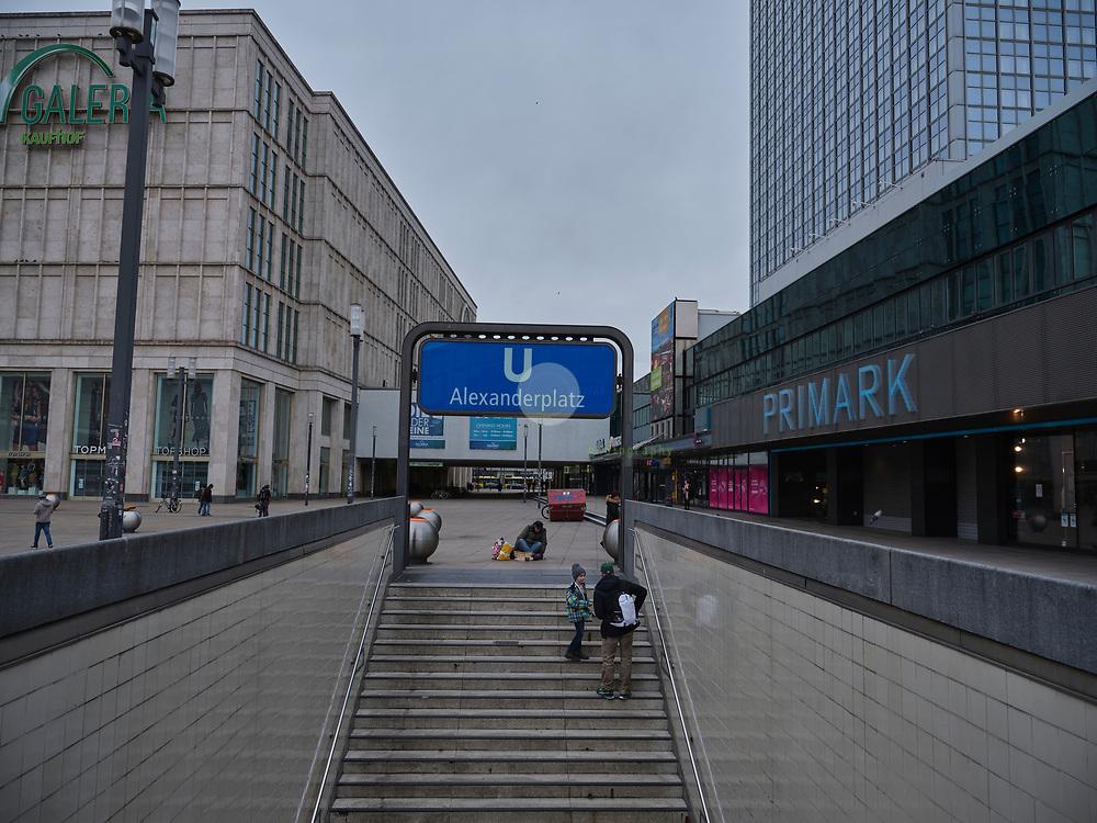 DEUTSCHLAND, Berlin, Alexanderplatz, 20.03.2020. Coronavirus-Pandemie: Wo an normalen Freitagnachmittagen tausende Menschen flanieren und einkaufen gehen, ist es an Tag 5 der der Coronavirus-bedingten Einschränkungen fast leer. Die meisten Geschaefte haben geschlossen, nur wenige Menschen benutzen die oeffentlichen Verkehrsmittel. Ein obdachloser Mann sitzt am U-Bahn-Ausgang.