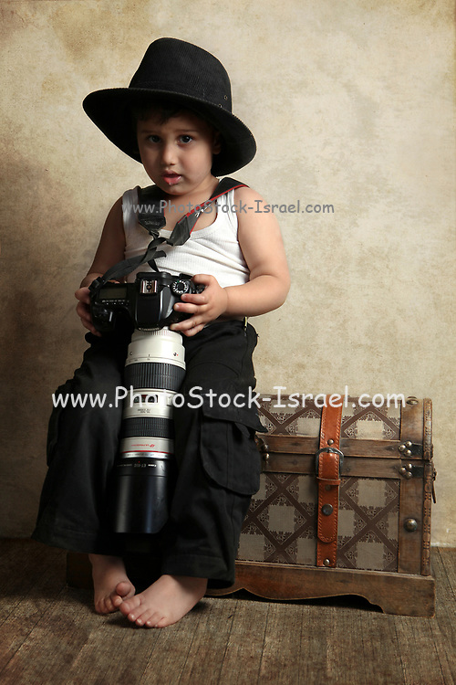 Young photographer sits on her travelling trunk ready to go out for an expedition