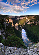 """A view at sunset of the Ardeche river and its gorges, which are actually a wonderful canyon - 35 kms long and 250 meters deep - the river dug for million years in a limestone plateau.  This part of the gorges is placed at about half lenght of the canyon and its main feature is the rock formation visible on the left of the river, know as """"La Cathédrale"""" for its vertical, sharp """"spires"""". Just to give a sense of scale of this scene, the Cathedral is about 80 meters tall, and I took this picture from a natural balcony at about 200 mts above the river bed. The slice of sky reflected in the river is so sharp and striking, that it almost looks like a rift in the Earth that let one look out to the other side of the planet. This is a stitch of four horizontal frames."""