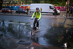 © Licensed to London News Pictures. 21/10/2021. London, UK. A commuter cycles through surface water on the Euston road in North London caused by heavy rain over night in the capital. Flash flooding hit parts of the south east as Storm Aurore brought winds of up to 45mph . Photo credit: Ben Cawthra/LNP