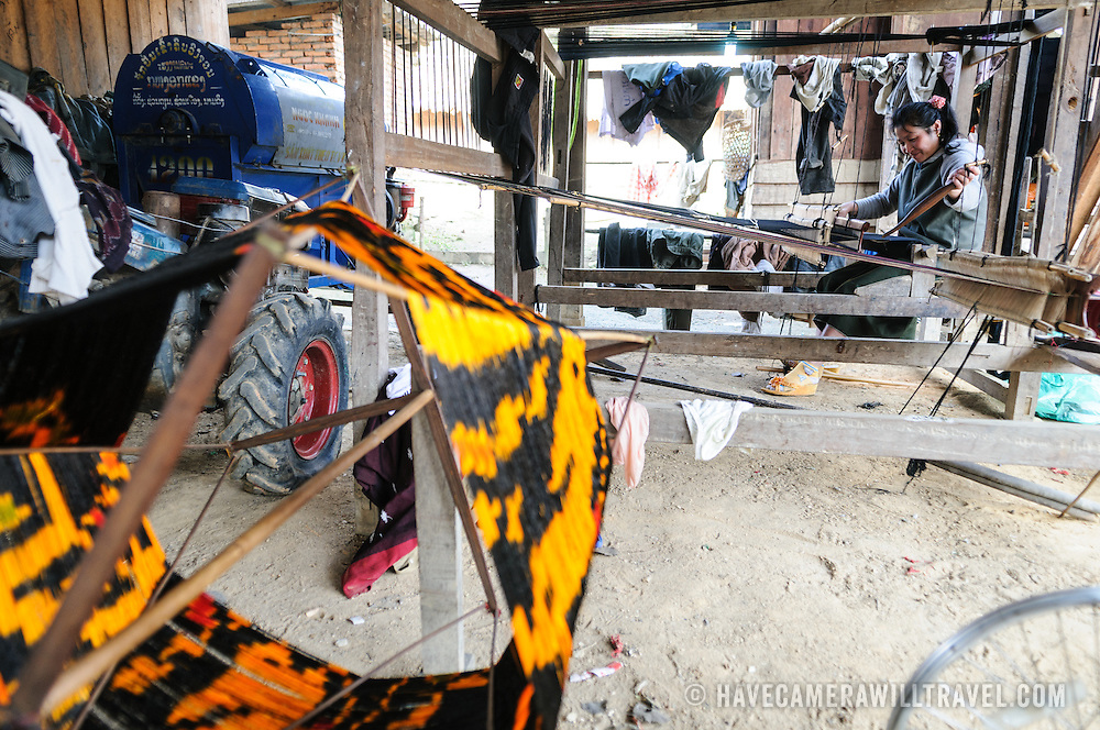 A woman using her loom on the dirt floor under her house in northeastern Laos. At right, in the foreground, is some of the brightly dyed silk thread she's using, and at bottom right you can see part of a bicycle wheel that has been repurposed for part of the spindle. At right is a tractor the family uses for farming.