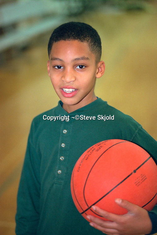 Teen age 13 holding basketball at community youth center.  St Paul Minnesota USA