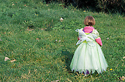 A young girl dressed as a fairy wondering of in the grass