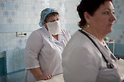 Doctor and nurse in Gomel Childrens regional hospital,Belarus. Chernobyl's human costs are widespread affecting about seven million people.A generation later children are being born with birth defects ,heart problems and thyroid cancer.The crippled economy of Belarus has led to poverty, social problems and domestic abuse.<br /> Photograph by Eamon Ward