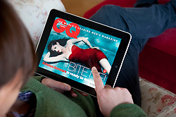 Woman using iPad tablet computer to read GQ magazine online edition