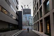 A male office worker or salaryman in a street in Kyobashi with the construction site of the Yaesu 2-chome redevelopment behind. Tokyo, Japan. Thursday April 1st 2021