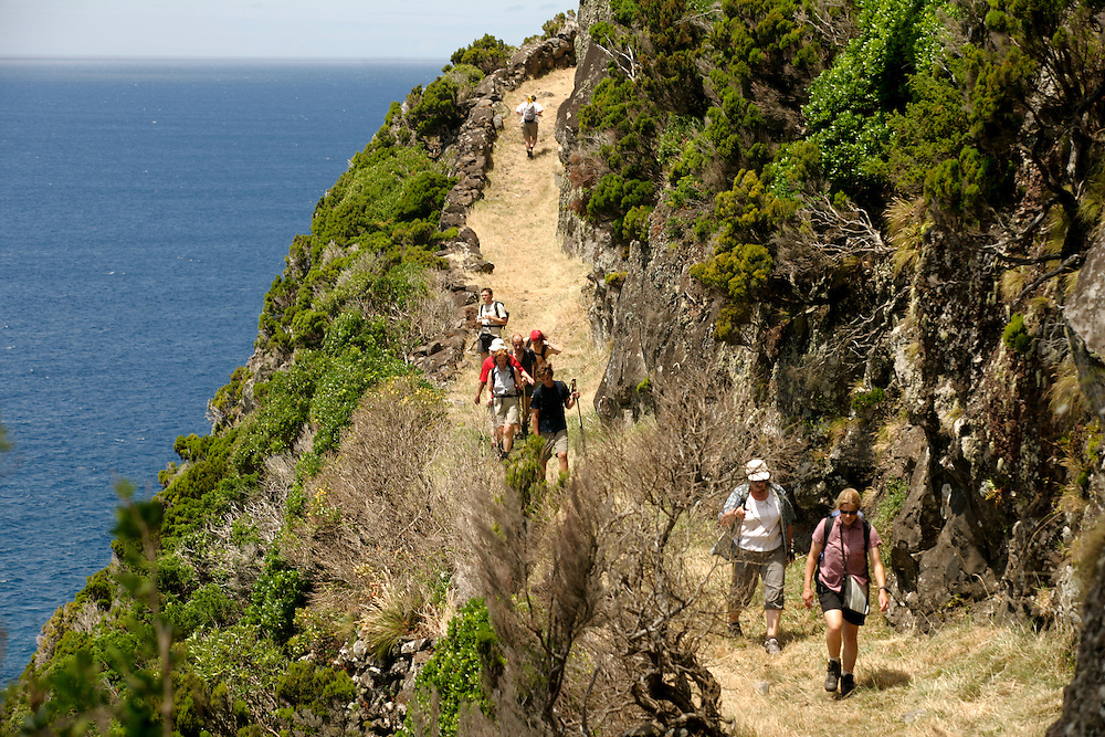 Tourists walking on the footpath that goes from Faj? Grande to Ponta Delgada in Flores island.