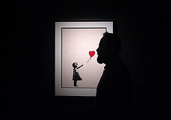 May 23, 2019 - Malaga, Spain - A man seen standing next a painting of 'Girl with balloon' during exhibition..'Bansky The art of Protest' at cultural center 'La Térmica' is an exhibition showing for the first time in Malaga. the work of famous and mysterious British street artist 'Bansky', display more than 40 creations such originals works, sculptures, videos and photographs provide by international private collections including the original print of ''Niña con globo' (Credit Image: © Jesus Merida Luque/SOPA Images via ZUMA Wire)