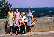 Family group portrait outdoors against wall smiling, British culture 1967 man, three women, boy child