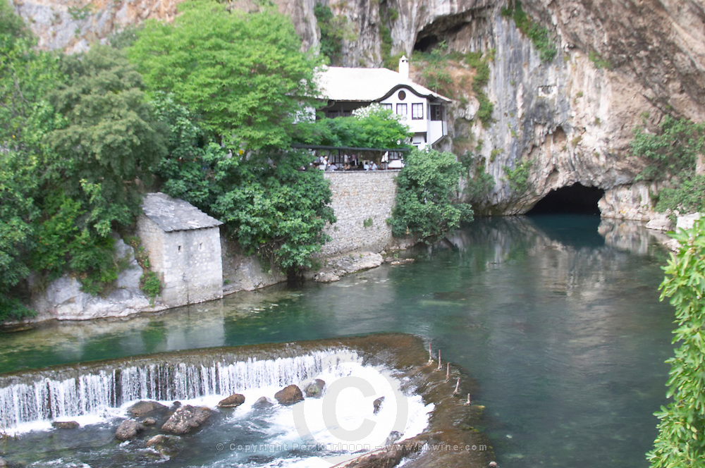 The source of the Buna river at the old Muslim monastery called the House of the Whirling Dervishes, below an impressive vertical cliff drop. Waterfall. The source of the Buna river and the house of the Whirling Dervishes, an old Muslim monastery, Blagaj. Federation Bosne i Hercegovine. Bosnia Herzegovina, Europe.