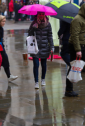 A woman's bright pink umbrellas brighten's a dull, wet, February Day at Piccadilly Circus. As forecasters predicted, the rain arrives in London where Londoners and tourists go about their business. London, February 13 2018.