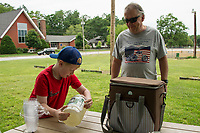 """Noah Sprague-Provencal pours a cup of his """"no cheating""""  fresh squeezed homemade lemonade for Kim during the American Legion Post 1 horseshoe tournament Saturday.  (Karen Bobotas/for the Laconia Daily Sun)"""
