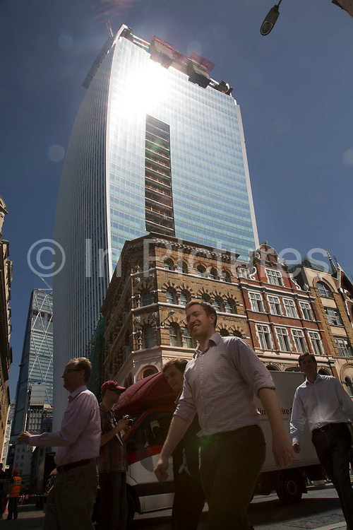 """London, UK. Thursday 5th September 2013. City workers pass below the building through a patch or reflectewd light. Urgent action in planned to """"cover up"""" the Walkie Talkie skyscraper in the City after sunlight reflected from the building melted a car on the streets below. Temperatures have been measured in excess of 50 degrees C, and as much as 70 degrees at it's peak. The 525ft building has been renamed the """"Walkie Scorchie"""" after its distinctive concave surfaces reflected a dazzling beam of light which has caused extensive damage to nearby buildings."""