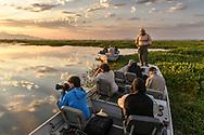 Touristen einer Fotoreise bei einem Bootsausflug bei Sonnenuntergang, Pantanal, Brasilien<br /> <br /> Tourists of a photo travel on a boat tour at sunset, Pantanal, Brazil