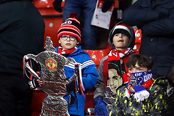 A Manchester United fan with a foil replica FA Cup trophy in the stands during the Emirates FA Cup, quarter final match at Old Trafford, Manchester.