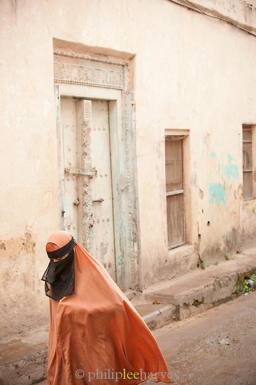 A local muslim woman walks along the narrow streets of Mombasa, Kenya