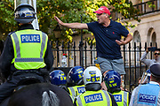 """A speaker of """"Resist and Act for Freedom"""" protest is seen calming his supporters prior to being arrested by the police as he addressed issues outside Downing Street, on Saturday, Sept 19, 2020. Protestors against a mandatory coronavirus vaccine, wearing masks, social distancing and a second lockdown, clashed with police nearby Canada House in Trafalgar Square. The event, which began at noon, drew a broad coalition including coronavirus sceptics, 5G conspiracy theorists and so-called """"anti-vaxxers"""". Speakers at the event accused the government of attempting to curtail civil liberties. (VXP Photo/ Vudi Xhymshiti)"""