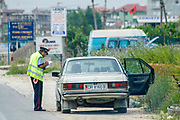 A policemen stops a vehicle for routine traffic control along the beach city of Durres as Albanian wealthy vacationers are seen enjoying a sunny day on Saturday, July 4, 2009. (Photo by Vudi Xhymshiti)