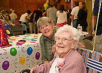 Brenda Moulton and her mother Gladys Burbank are greeted by dozens of family and guests during Gladys' surprise 100th birthday celebration held at Leavitt Park on Saturday afternoon.  (Karen Bobotas/for the Laconia Daily Sun)