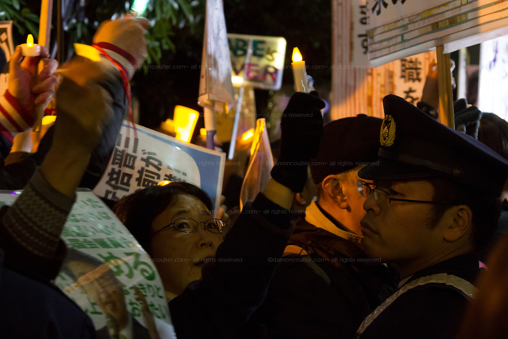 Hundreds of students and other activists hold candles and signs as they  protest outside the Japanese Prime Minister's office calling on the Japanese Prime Minister, Shinzo Abe and Finance Minister, Taro Aso to resign over a suspected cover-up of the Moritomo Gakuen school  land sale scandal and falsified documents. Kasumigaseki, Tokyo, Japan Friday, March 23rd 2018