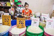 "03 OCTOBER 2012 - BANGKOK, THAILAND:      A rice vendor in Khlong Toey Market. Thailand is the leading rice exporter in the world. Khlong Toey (also called Khlong Toei) Market is one of the largest ""wet markets"" in Thailand. Thousands of people shop in the sprawling market for fresh fruits and vegetables as well meat, fish and poultry every day.       PHOTO BY JACK KURTZ"