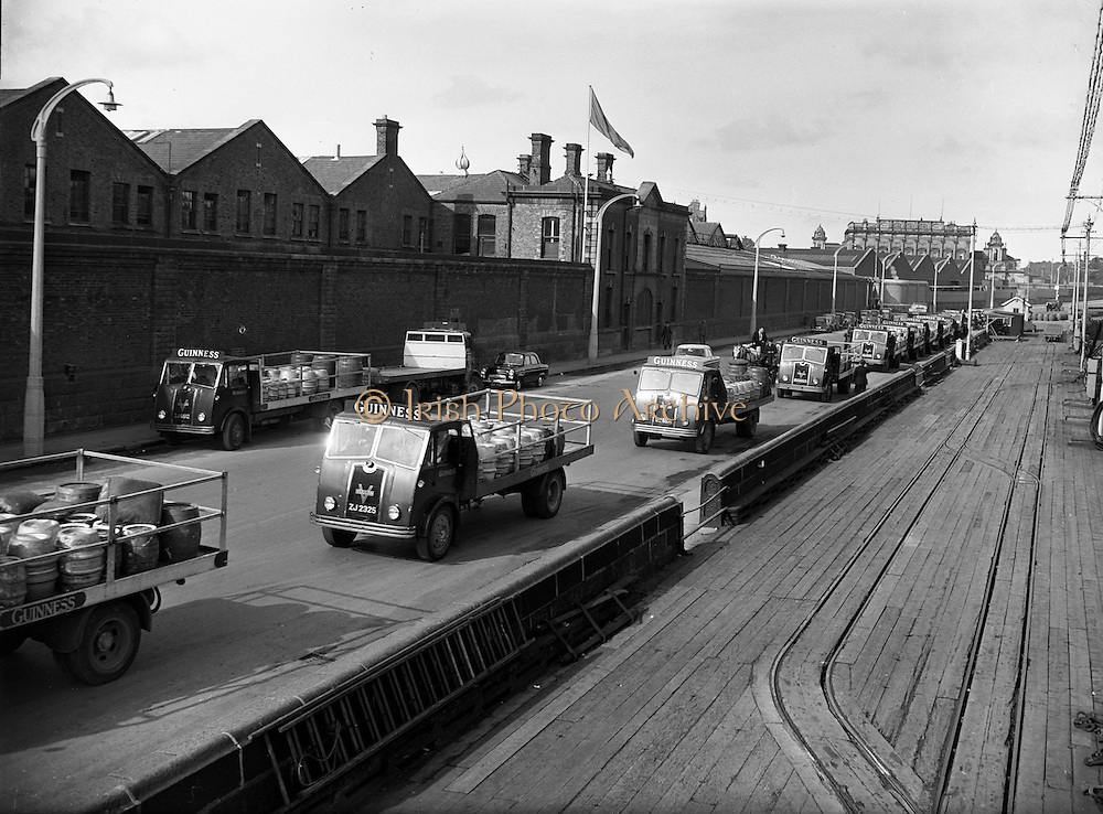 23/08/1958<br /> 08/23/1958<br /> 23 August 1958<br /> Guinness transport on the wharf outside St James's Gate Brewery, Dublin. Image shows the fleet of Vulcan fallback trucks. Houston train station visible in background.