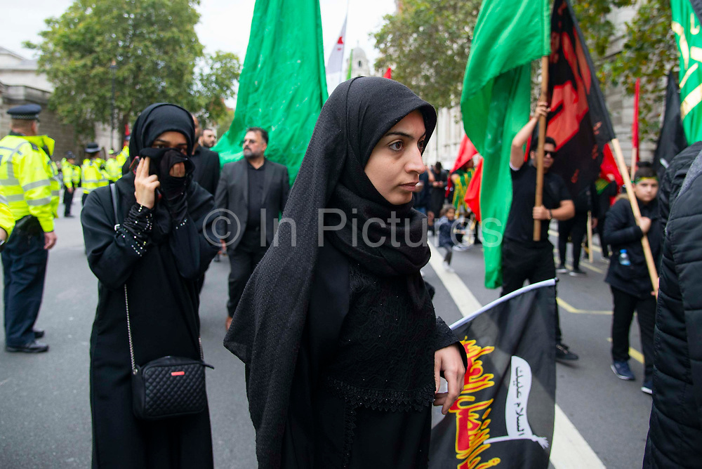 Devote Shia Muslim women wearing traditional black chadors commemorate the festival of Ashura in Whitehall, London, United Kingdom on 10th Spetember 2019. It marks the day that Husayn ibn Ali, the grandson of the Islamic prophet Muhammad, was martyred in the Battle of Karbala. Ashura is the tenth day of Muharram, the first month in the Islamic calendar.