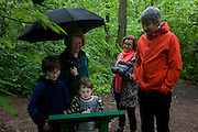 A family read information from a board in woods south of Sheffield, England UK.