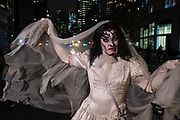 New York, NY - 31 October 2019. the annual Greenwich Village Halloween Parade along Manhattan's 6th Avenue. A man dressed as a bride, with very red lips, and heavy-metal styled makeup.