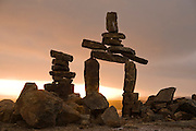 Inukshuk (stone marker) above the town of Iqaluit, Nunavut, Canada. An inukshuk is a stone landmark used as a milestone or directional marker by the Inuit of the Canadian Arctic.  The Arctic Circle, dominated by permafrost, has few natural landmarks and thus the inukshuk was central to navigation across the barren tundra.