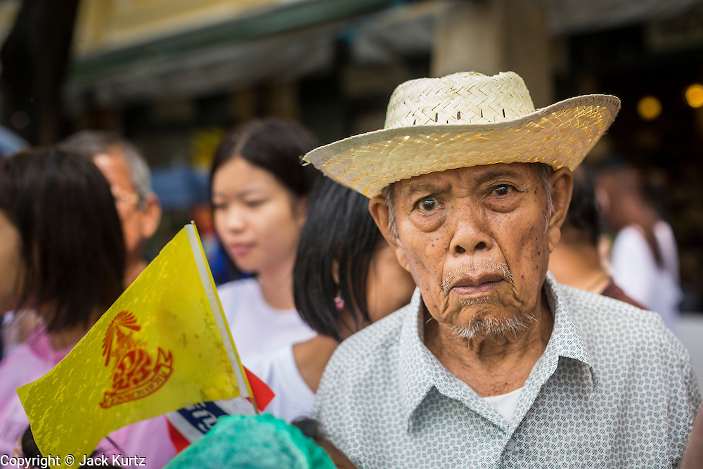 """05 MAY 2013 - BANGKOK, THAILAND:   A Thai man waits to see Bhumibol Adulyadej, the King of Thailand, Sunday. The King and Queen, who are both hospitalized and in poor health, did not attend Sunday's event. May 5 marks the 63rd anniversary of the Coronation of His Majesty King Bhumibol Adulyadej. The day is celebrated as a national holiday; since this year it falls on a Sunday, it will be observed on Monday May 6, and as such all government offices and commercial banks will close for the day. HM King Bhumibol Adulyadej is the longest reigning monarch in the world. Each year on the 5th of May, the Kingdom of Thailand commemorates the day when, in 1950, the Coronation Ceremony was held for His Majesty King Bhumibol Adulyadej, the 9th in the Chakri Dynasty (Rama IX). On the 5th of May, His Majesty conducts a merit making ceremony, presenting offerings to Buddhist monks, and leads a """"Wien Thien"""" ceremony, walking three times around sacred grounds at the Temple of the Emerald Buddha.    PHOTO BY JACK KURTZ"""
