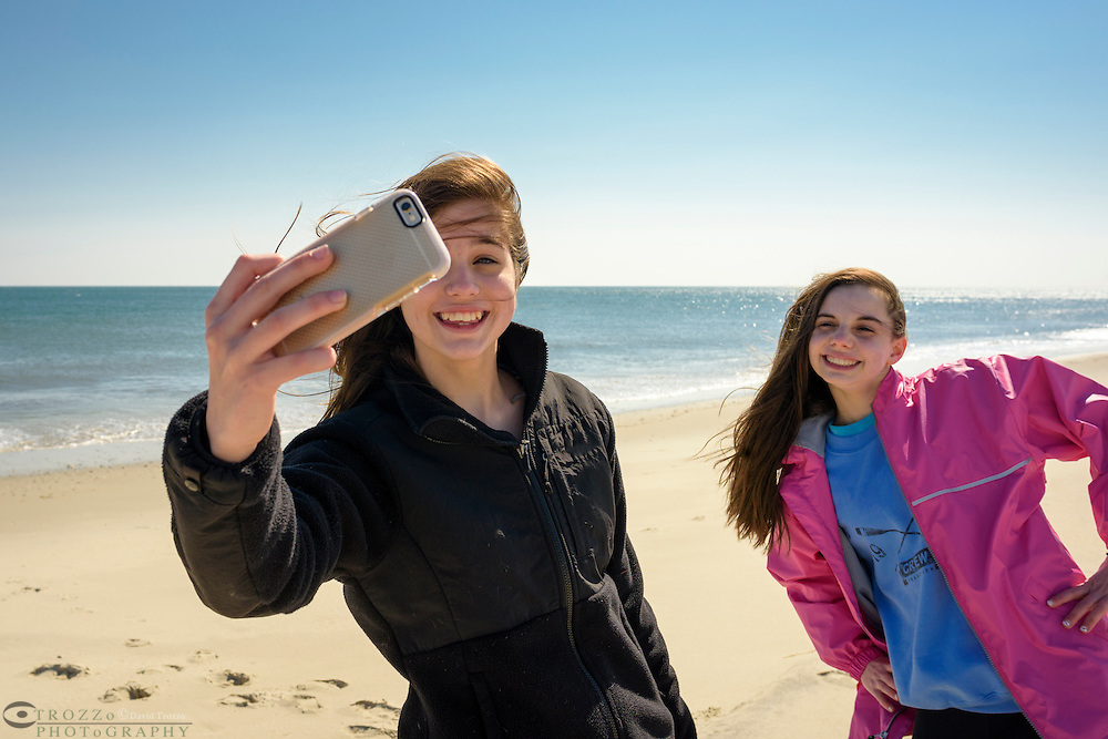 Young teens taking a selfie on the beach, Cape May, New Jersey.
