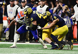 Michigan Wolverines fullback Ben Mason (42)  blocks Florida Gators defensive back Quincy Lenton (27) as Michigan Wolverines wide receiver Ronnie Bell (8) attempts to get yardage during the Chick-fil-A Bowl Game at  the Mercedes-Benz Stadium, Saturday, December 29, 2018, in Atlanta. ( Kyle Hess via Abell Images for Chick-fil-A Kickoff)