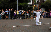 UK, July 7 2012: Paul Draper carries the Olympic Torch in Moulsham Street towards Oaklands park on on Saturday 7th July 2012. Copyright 2012 Peter Horrell.