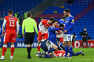 Cardiff City's Kieffer Moore (10) is helped to his feet by his Captain Sean Morrison (4) after a clash of heads during the EFL Sky Bet Championship match between Cardiff City and Millwall at the Cardiff City Stadium, Cardiff, Wales on 30 January 2021.