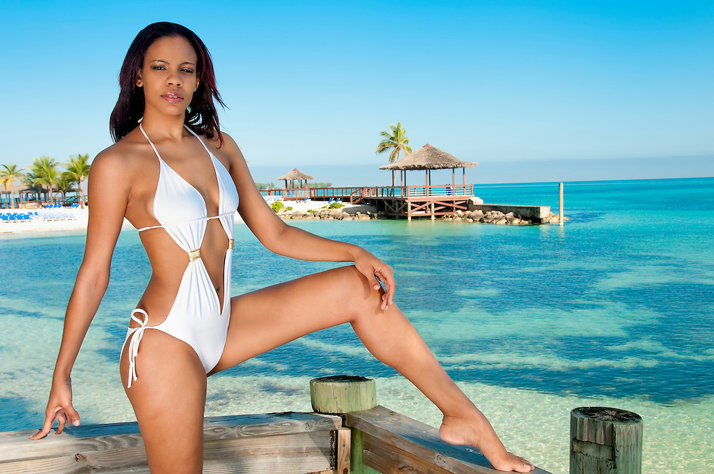 Young bahamian woman enjoys the beach in a resort.