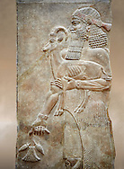Stone relief sculptured panel of a man holding an Ibex and a poppy flower. Facade L. Inv AO 19872 from Dur Sharrukin the palace of Assyrian king Sargon II at Khorsabad, 713-706 BC.  Louvre Museum Room 4 , Paris .<br /> <br /> If you prefer to buy from our ALAMY PHOTO LIBRARY  Collection visit : https://www.alamy.com/portfolio/paul-williams-funkystock/ancient-assyria-antiquities.html  Refine search by adding background colour, place, subject, museum etc into the LOWER SEARCH WITHIN GALLERY box to <br /> <br /> Visit our ANCIENT WORLD PHOTO COLLECTIONS for more photos to download or buy as wall art prints https://funkystock.photoshelter.com/gallery-collection/Ancient-World-Art-Antiquities-Historic-Sites-Pictures-Images-of/C00006u26yqSkDOM